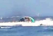 TERBALIK: Perahu terbalik di Pantai Pancer, Kecamatan Puger, Jember, akibat dihantam ombak yang terekam warga sekitar. | Foto: Ist
