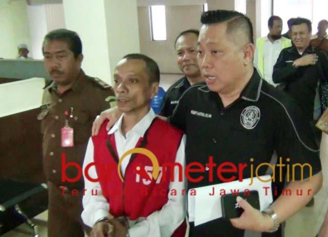 KESANDUNG GANJA: Hubert Henry (tengah) menuju ruang persidangan di PN Surabaya. | Foto: Barometerjatim.com/ROY HS