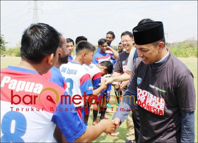 FOOTBALL FOR PEACE: Gus Hans (berkopiah) menyalami para pemain Uni Papua sebelum kick-off laga perdamaian. | Foto: Barometerjatim.com/ROY HS