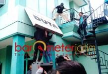 DITURUNKAN: Papan Duta Masyarakat ikut diturunkan saat eksekusi Astranawa. | Foto: Barometerjatim.com/ABDILLAH HR