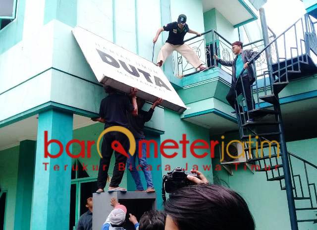 DITURUNKAN: Papan Duta Masyarakat ikut diturunkan saat eksekusi Astranawa.   Foto: Barometerjatim.com/ABDILLAH HR