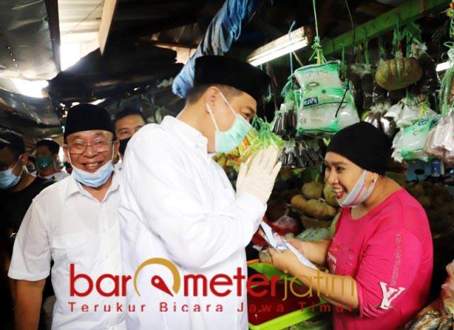 BERSAPA HANGAT: Didampingi Haji Masnuh, Kelana Aprilianto bersapa hangat dengan pedagang pasar. | Foto: Barometerjatim.com/ROY HS