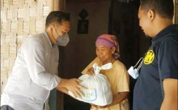 SEMBAKO: Zulfahmy Wahab (kiri) bersama komunitasnya membagikan paket sembako secara door to door.   Foto: Barometerjatim.com/IST