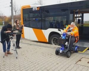 Am Set: Wolfgang Lang (sitzend im E-Scooter) fährt mit dem E-Scooter aus dem RNV-Bus.