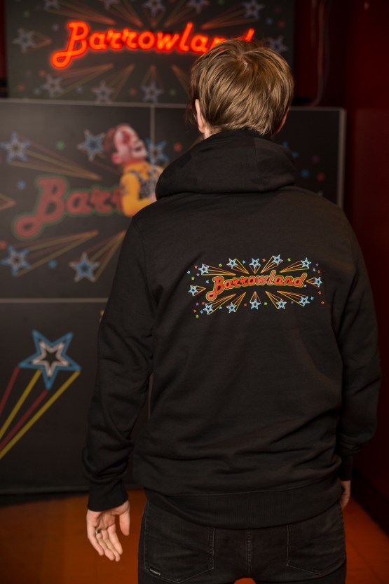 Man showing back print of Black Barrowland hooded top