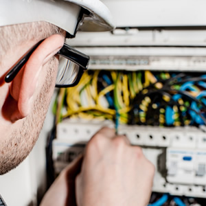 An electrical engineer using tools on a fuse board