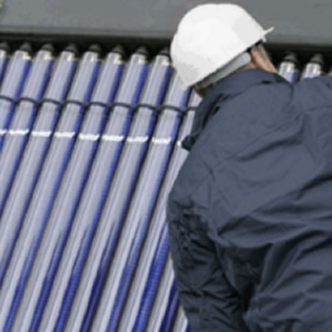 A man installing solar thermal panels wearing a white hard hat