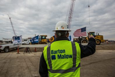 Builder surveying job site with American flag in background