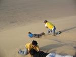 Bas op haar buik de zandduin af