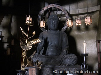 A Buddha hidden in the back of a giant statue