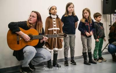 Enfants chantant avec leur animatrice à la guitare de l'association Bas les Masques
