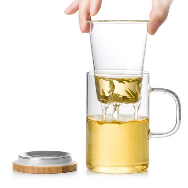 Glass mug with infuser basket being taken out of mug