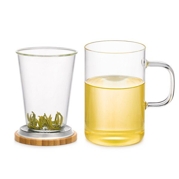 Glass mug with infuser basket sitting on bamboo lid