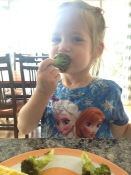 Dr. Danielle's daughter snacking on broccoli