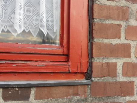 Altes morscher Fensterrahmen aus Holz mit abblätternder Farbe