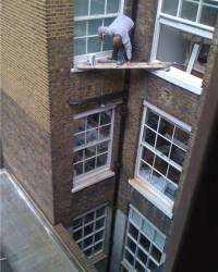 Streichen von Fensterrahmen in 4. Etage auf einer Holzbohle