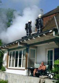 Mann sitzt auf Veranda Terrasse während der Dachstuhl brennt