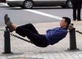 Mann schläft auf einer Eisenkette an der Straße