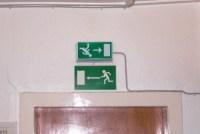 Zwei Schilder für Fluchtwege in entgegengesetzter Richtung