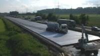 Betonwagen fährt auf Autobahnbaustelle durch frischen Beton