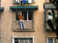 Frau steht außen auf Fenstersims und putzt Fenster