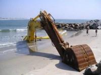 Bagger im weichen Sandstrand versunken, nur Schaufel ist sichtbar