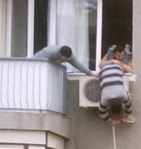 Mann montiert Klimaanlage Splittgerät aus dem Fenster hängend