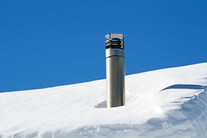 Schornstein aus Edelstahl auf schneebedecktem Dach