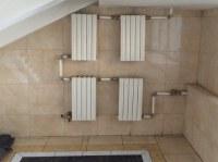 4 kleine Heizkörper an der Wand im Badezimmer