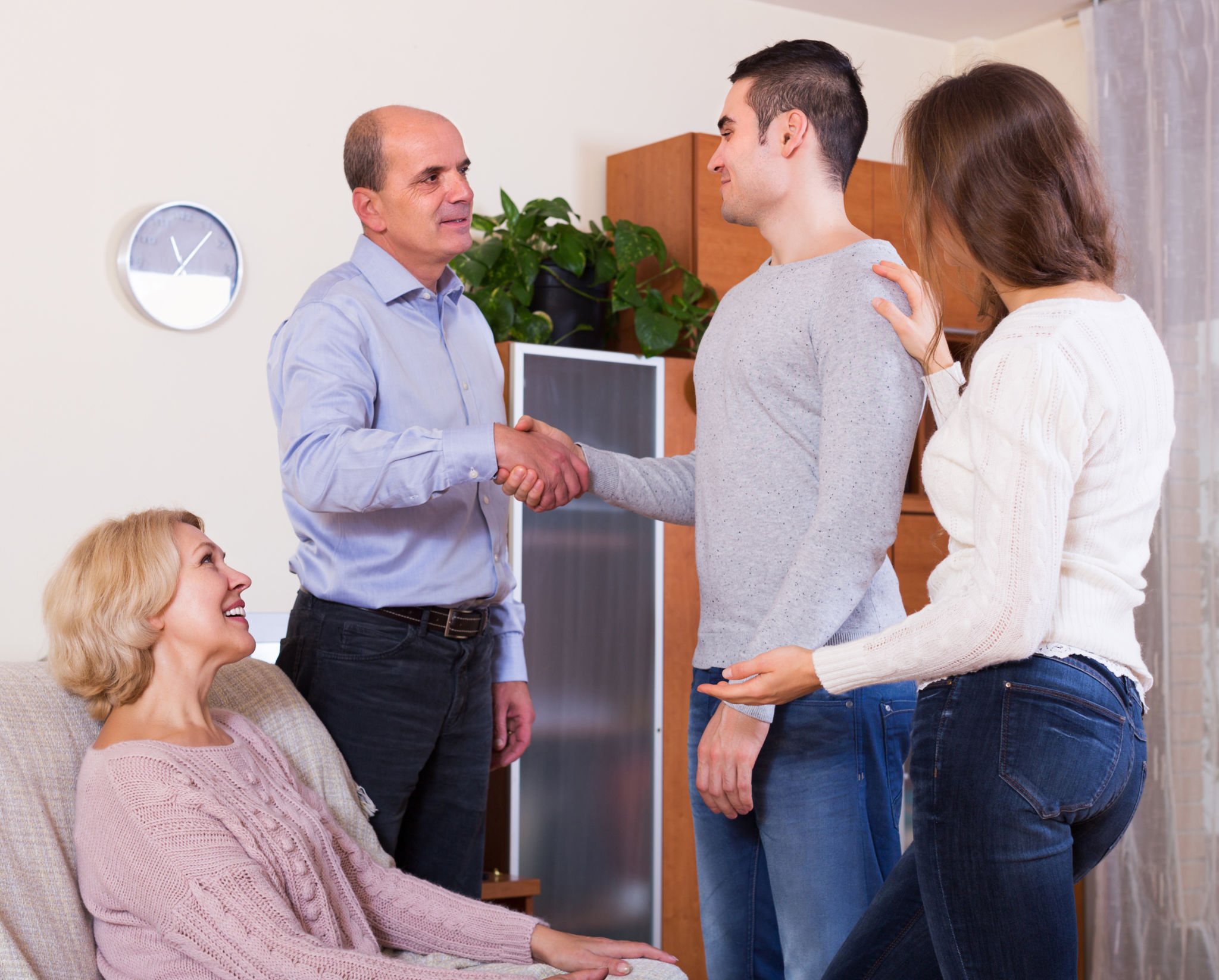 image of a man meeting the parents and shaking hands with girlfriend's father.