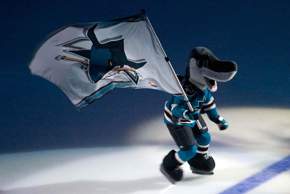 Sharkie of the San Jose Sharks carrying a flag across the ice