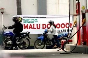 """Motorad Fahrer die zum Tanken bei der Premiumtanksäule stehen werden mit einem Transparent begrüßt """"Ihr tankt Premium - Schämt euch! Fot: JP / PJ Leo Fotoquelle: Jakarta Post"""