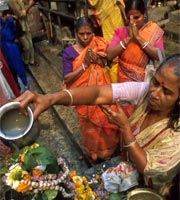 Indian women making offering to Shiva on the Ganges, Calcutta, India