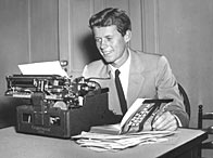 Future American president John F Kennedy, sits at a typewriter, holding open his published thesis, 'Why England Slept' (c. 1940)