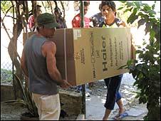 Personas cargando un refigerador / Foto: Raquel Pérez