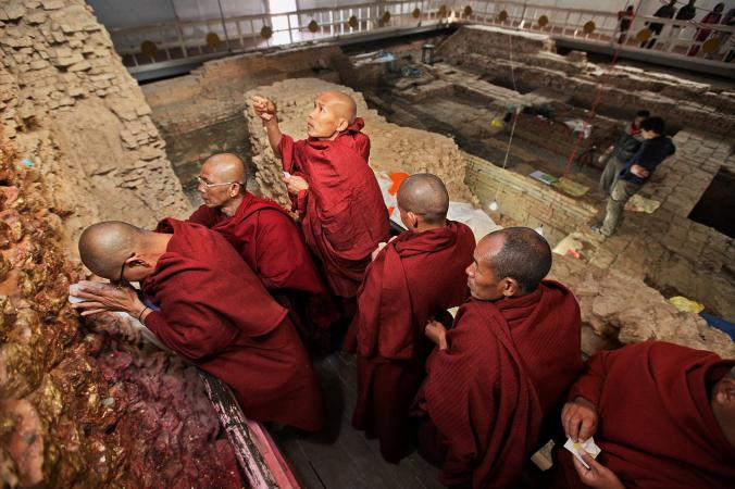 Pilgrims meditate in the Maya Devi Temple at Lumbini, Nepal. The remains of the earliest temples at the site are in the background.  PHOTOGRAPH BY IRA BLOCK, NATIONAL GEOGRAPHIC