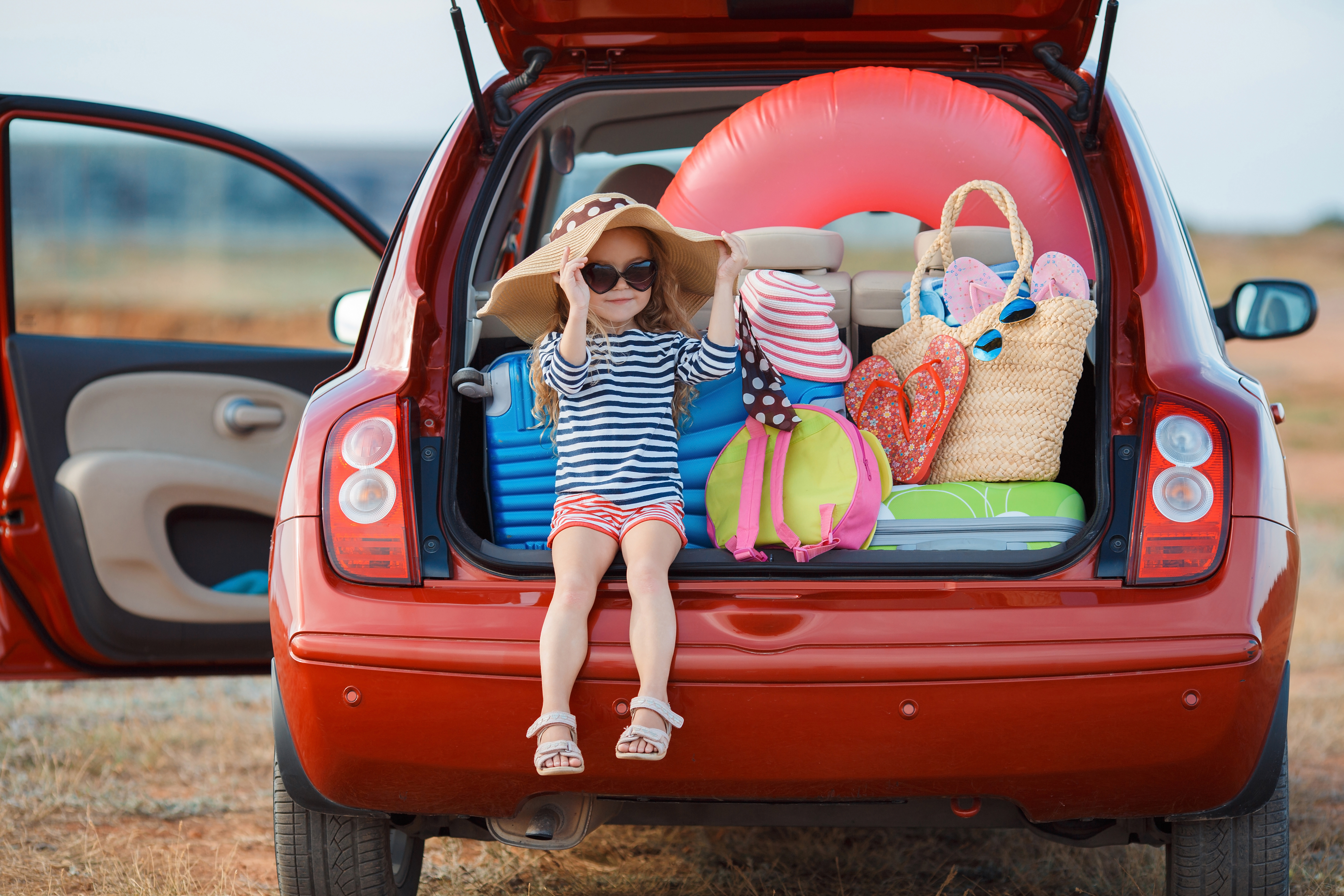 bbnove e-shop puériculture design - concept store made in france pour bébés Little girl in straw hat sitting in the trunk of a car