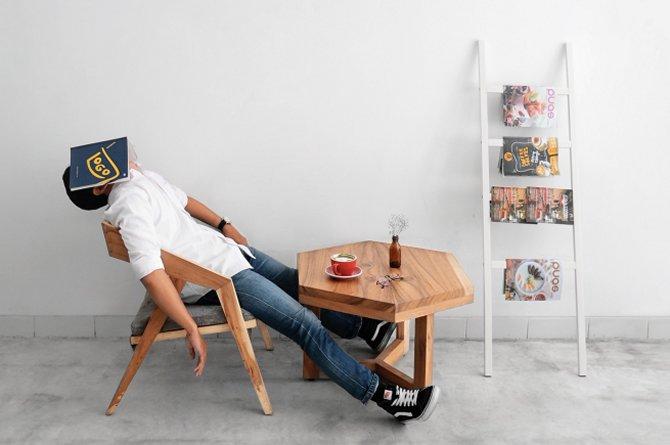 Mann sitzt und schläft mit Buch vorm Kopf