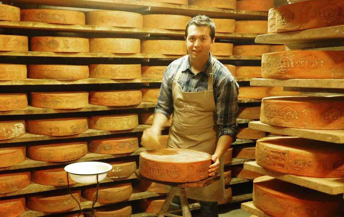 Andrea Pelizzari durante la pulitura del formaggio Bagoss di Bagolino