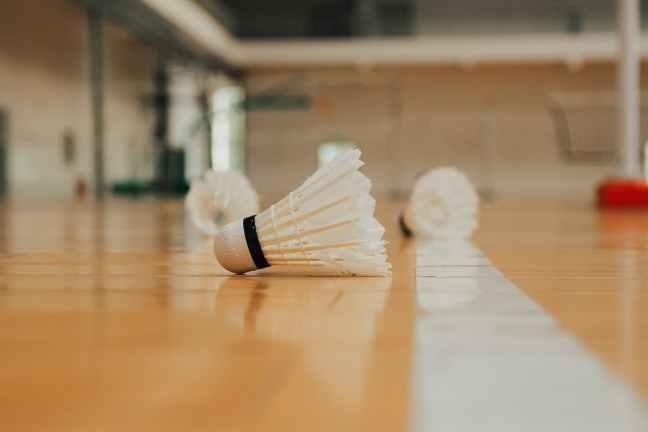 shuttlecocks on wooden floor in sports hall