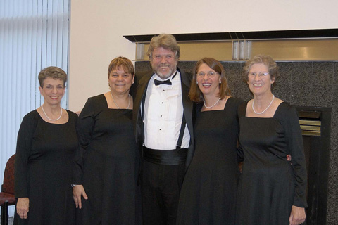 """The Falls Church contingent of the New Dominion Chorale models new concert garb, smart black dresses for women replacing the white blouse/black skirt costume.No change in the men's dress. From left, Beverly Laub, Rosemarie Hunziker, James Oglethorpe, Renee Andrews, Jennifer Heffernan, all of Falls Church. The Chorale's holiday concert, featuring Bach's """"Magnificat,"""" Conductor Thomas Beveridge's new """"Magnificat"""" and singalong carols, takes place at  4:00 pm, Sunday, Dec. 3, at the Schlesinger Center in Alexandria. Tickets are $25; $20 for seniors; $5 for students; and $20 for group sales. Free parking. Purchase tickets online at www.newdominion.org; by phone, 703-442-9404; or in person at Foxes Music, Falls Church, or Maley's McLean Music, McLean."""