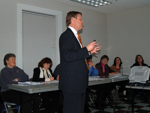 HEKEMIAN COMPANY'S Senior Vice President Chris Bell (standing) is shown presenting his company's latest plan for development of the old Pearson Funeral Home site on N. Washington to a joint work session of the Falls Church City Council and Planning Commission Monday. Identifiable Planning Commissioners shown seated are (left to right) Suzanne Fauber, Ruth Rodgers and Maureen Budetti. Far right are City Planning staffers Wendy Sanford and Elizabeth Friel. (News-Press photo)