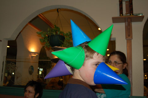 A POTENTIAL CANDIDATE for the Guiness Book of Records, 12-year-old Eric Clinton successfully planted nine party hats, all totally in contact with his head, as a highlight of the birthday party at Anthony's Restaurant last Friday honoring News-Press owner-editor Nicholas F. Benton. Eric's dad, Tom Clinton, Falls Church Commissioner of the Revenue, was among the 36 guests, including Mayor Robin Gardner and Vice Mayor Lindy Hockenberry and Councilman David Snyder.  (Photo: News-Press)