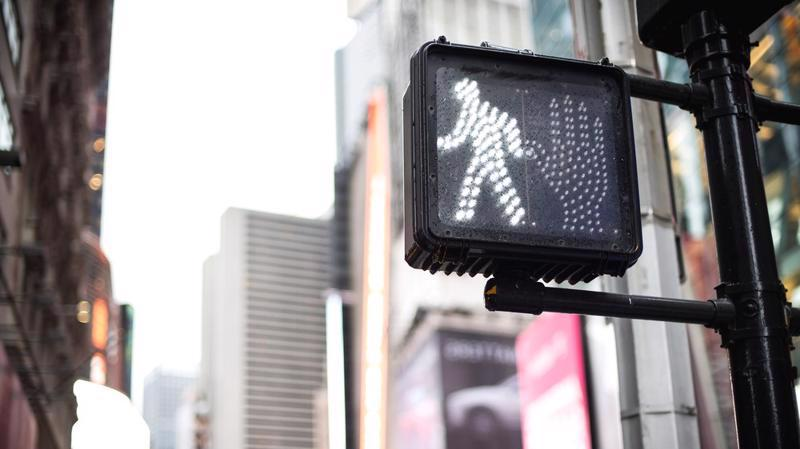 A pedestrian crosswalk sign is shown telling walkers it is safe to walk.