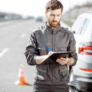 A man signs documents at roadside after a motorcycle accident.