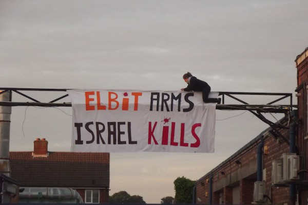 Protester-hangs-_Elbit-Arms-Israel-Kills_-at-shutdown-Elbit-factory-in-Birmingham.-The-factory-produces-drone-engines-which-are-exported-to-Israel-and-used-over-Gaza-copy