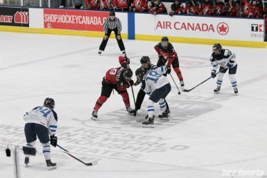 Canada's Jennifer Wakefield #9 and Finland's Tanja Nishkanen face off at center ice.