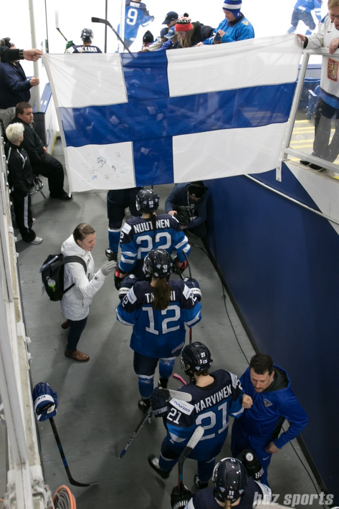 Team Finland entering the ice under the Finnish flag.