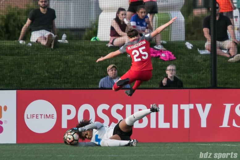 Portland Thorns FC defender Meghan Klingenberg (25) hurdles over Boston Breakers goalkeeper Abby Smith (14).