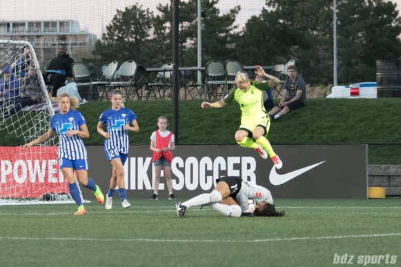 Breakers' Abby Smith smothers the ball as Reign FC's Jess Fishlock #10 jumps to avoid a collision.